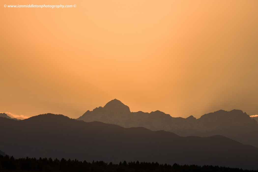 Sun setting behind Mount Triglav, the highest mountain in the Julian Alps, Slovenia.