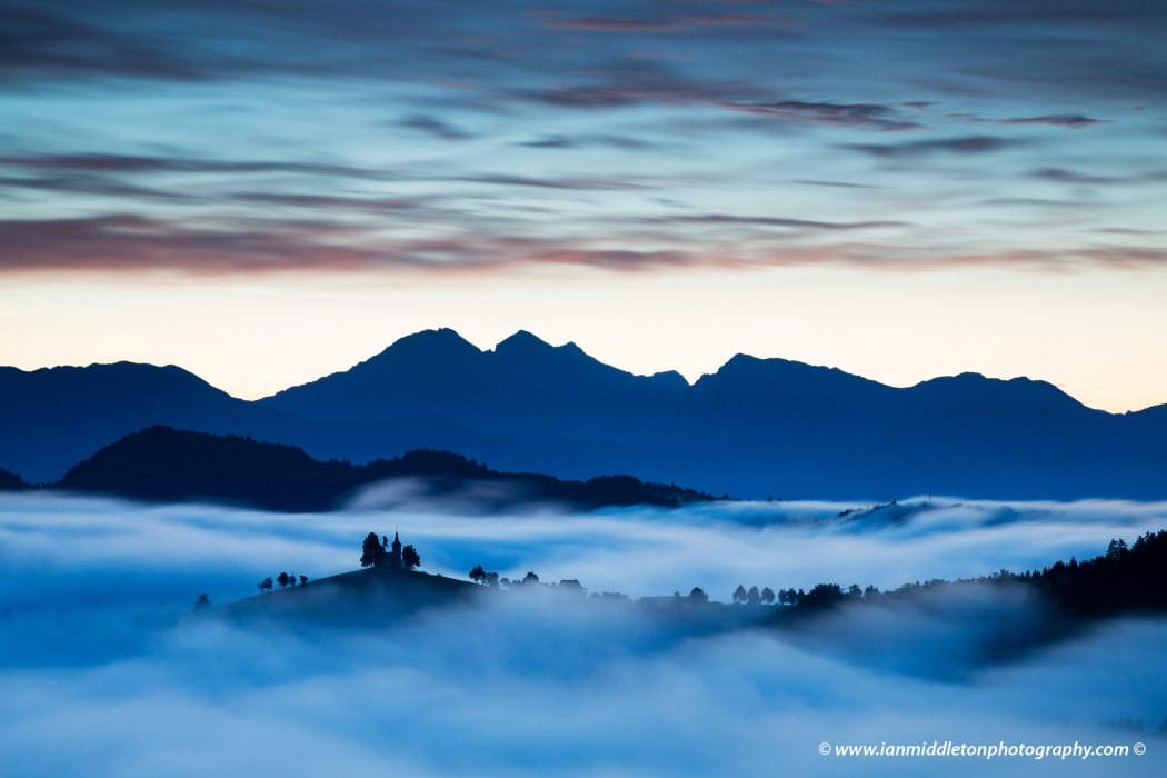 View at dawn from Rantovše hill across to Sveti Tomaz nad Praprotnim (church of Saint Thomas) and the Kamnik Alps, Slovenia.