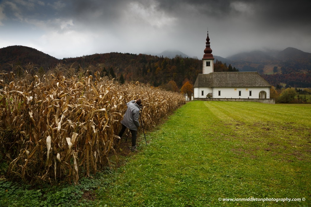Student photographing church just outside Bohinjska Bistrica, Bohinj, Triglav National Park, Slovenia.
