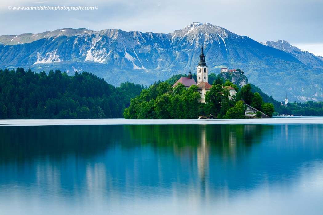 All in one view across to the beautiful island church of the assumption of Mary, Bled Castle and the Church of Saint Martin, all backed by Mount Stol and the Karavanke alps, Lake Bled, Slovenia.
