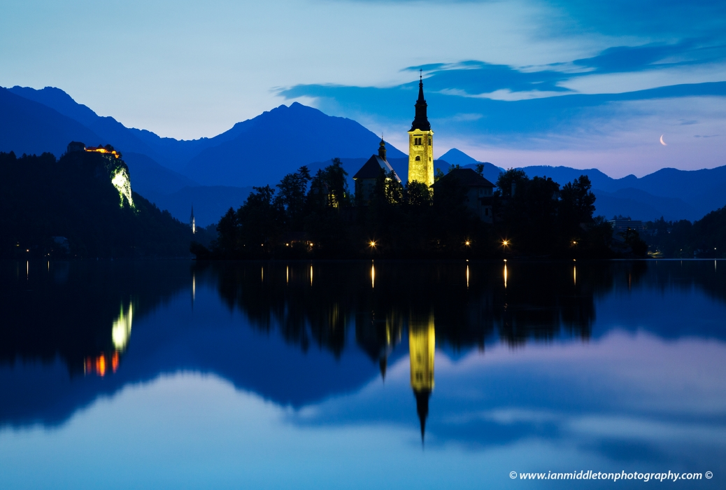 View across the beautiful Lake Bled, island church of the assumption of Mary, and hilltop castle, all topped off with the crescent of the waning moon at dawn, Slovenia.