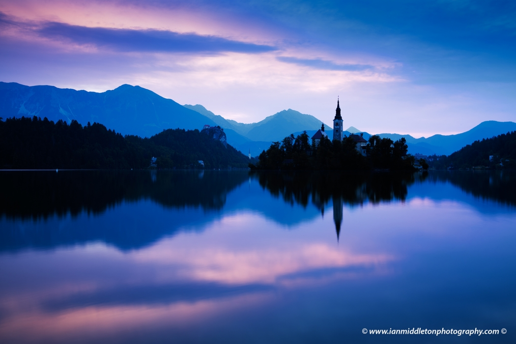 Sun at Lake Bled and the island church of the assumption of Mary with the Karavanke mountains in the background, Slovenia. To the left of the church is Mount Stol, the highest peak in the Karavanke mountain range.