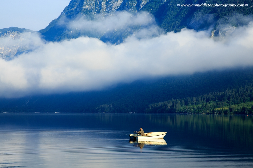 Man on his boat in the morning at Lake Bohinj, Triglav National Park, Slovenia
