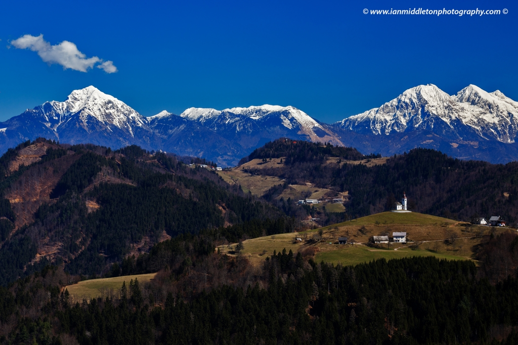 View from Rantovše hill across to Sveti Tomaz nad Praprotnim (church of Saint Thomas) and the Kamnik Alps, Slovenia.