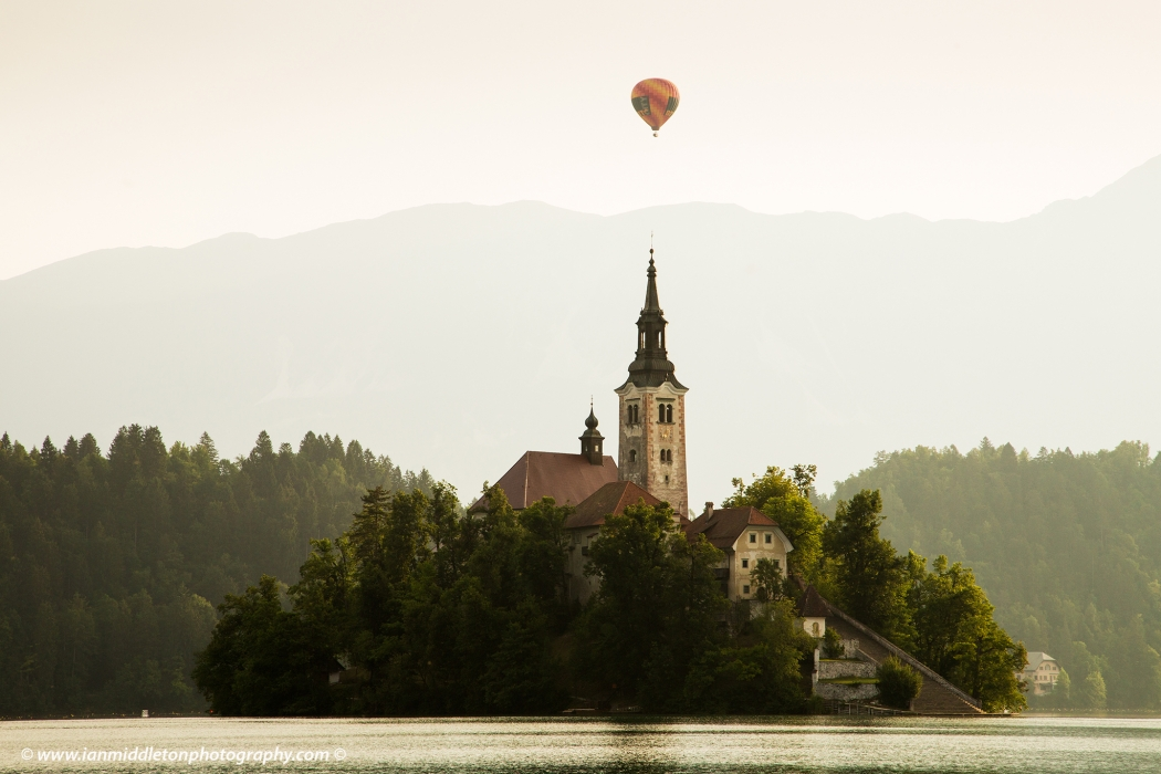 A hot air balloon rising over the mountains behind Lake Bled's island church, Slovenia.