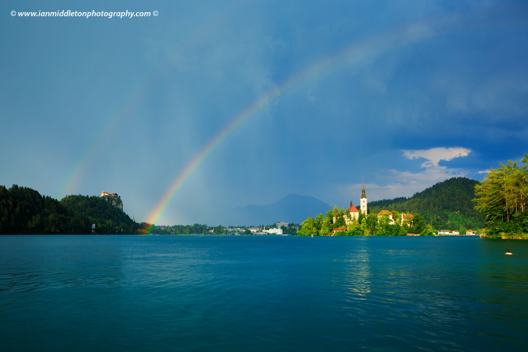 Woman swimming out into Lake Bled as a double rainbow appears over the island church and hilltop castle, Slovenia.