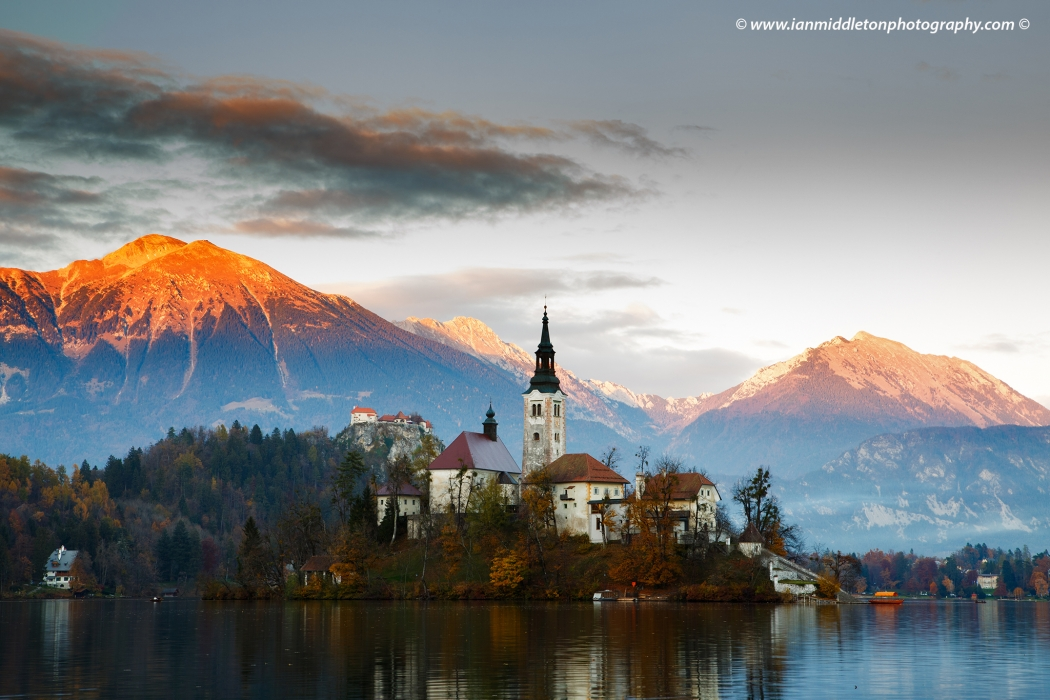View across the beautiful Lake Bled, island church and hilltop castle at sunset with the beautiful Karavanke mountains in the background, Slovenia. Lake Bled is Slovenia's most popular tourist destination and the Karawanke mountains form the border between Slovenia and Austria.