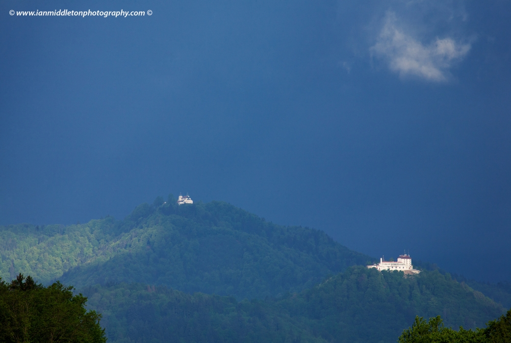 Morning sunlight breaks through the storm clouds and illuminates the church of Saint Judoc (Slovene: sveti Jošt) on a hill overlooking the city of Kranj, the second largest city in Slovenia.