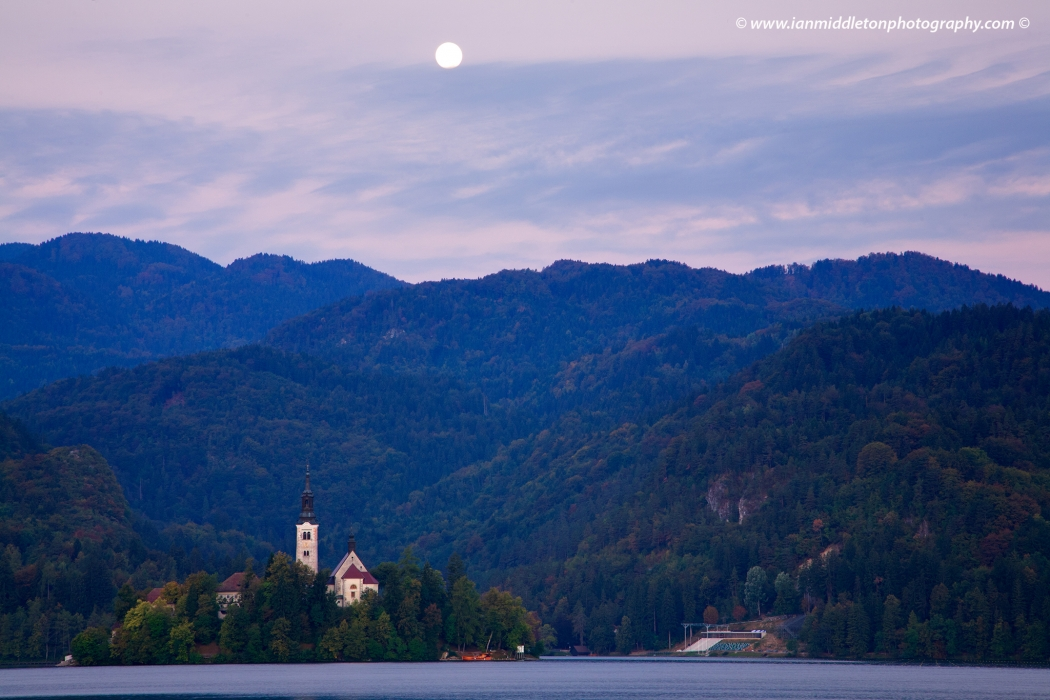 Moon setting at sunrise over hills and Island church at Lake Bled , Slovenia .