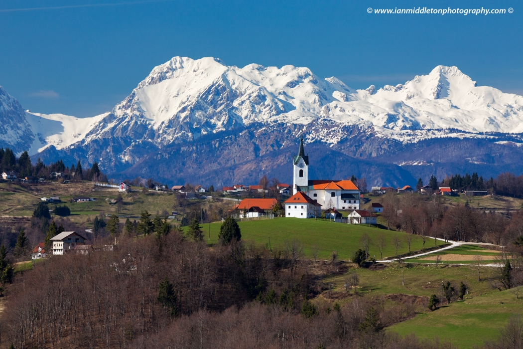 The church of Saint Marjeta in Prezganje in the Jance hills to the east of Ljubljana, Slovenia. The snow covered Kamnik Alps form a beautiful backdrop.