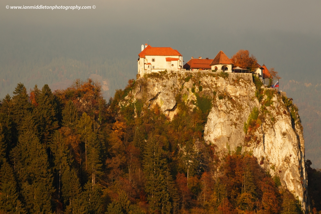 Close up view across Lake Bled to the clifftop castle in all it's autumn glory, Slovenia.
