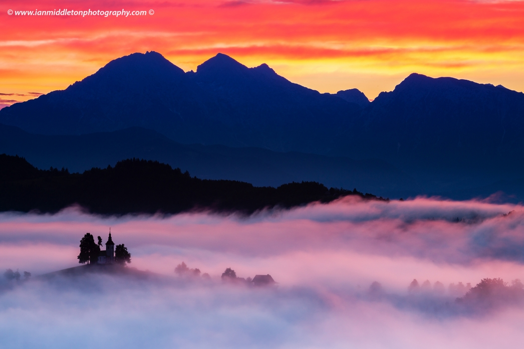 View at sunrise from Rantovše hill across to Sveti Tomaz nad Praprotnim (church of Saint Thomas) and the Kamnik Alps, Slovenia.