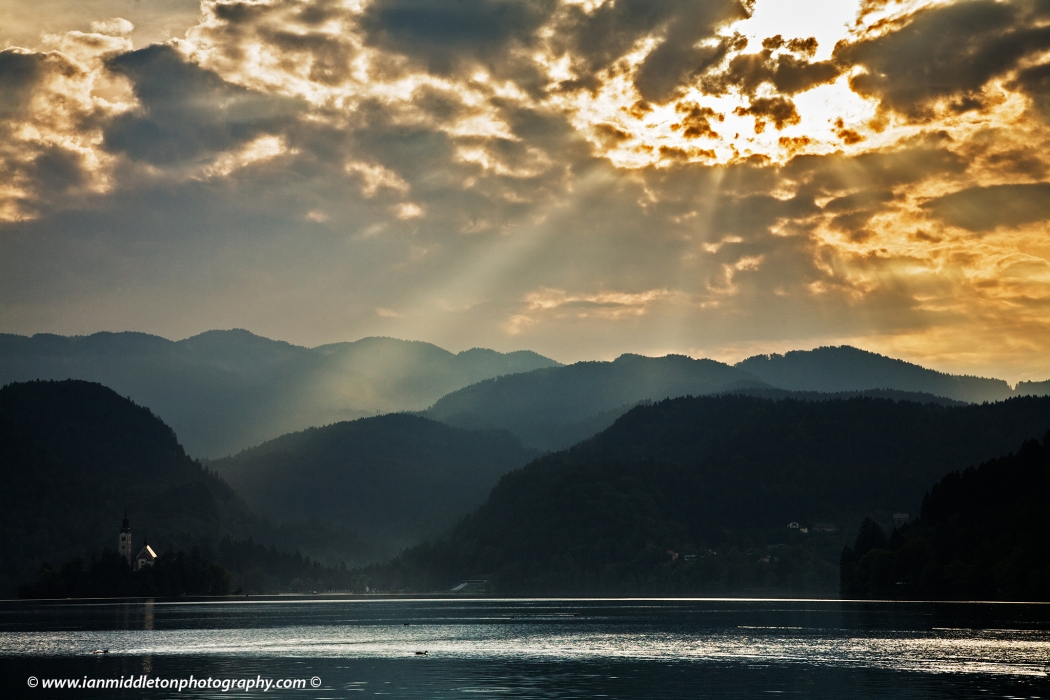 Sun bursting through the clouds and sunrays illuminating the Island Church and mountains in the background, Bled Lake, Slovenia. Some people refer to this beautiful spectacle of nature as angel rays from heaven. Lake Bled is Slovenia's most popular tourist destination.