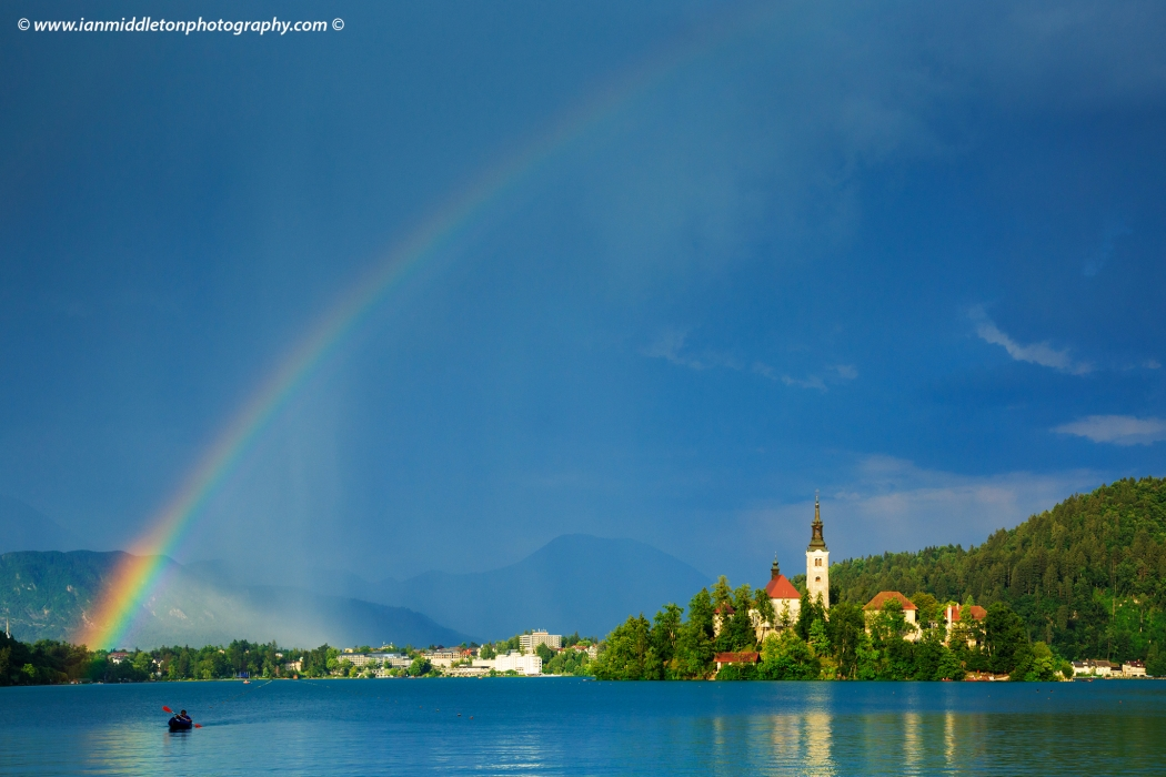 Beautiful light across to the beautiful Lake Bleds island church as a storm blows in and produces a rainbow right over the church and surrounding hills, Slovenia.