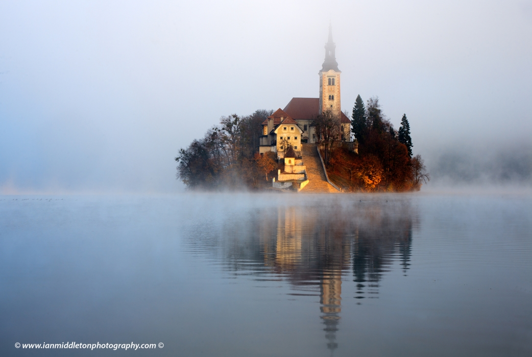 The famous Island church emerging as the morning sun breaks through an icy mist over Lake Bled.